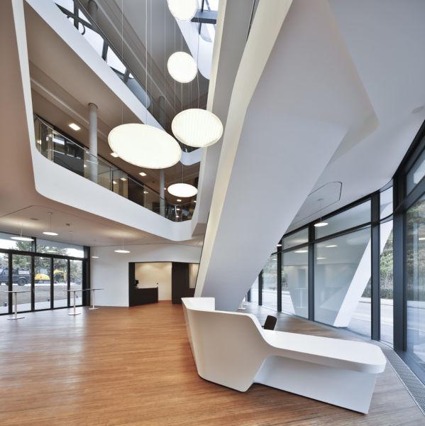 L'interazione tra le forme decise delle lampade e l'ampia apertura dell'atrio crea una particolare atmosfera (©Martin Duckek)